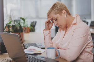 Woman sitting at desk at work with migraine pain, if struggling with disability coverage meet with Chicago Loop Long Term Disability Benefits Attorney.